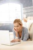 Mujer joven que usa la computadora portátil en el sofá Imagenes de archivo