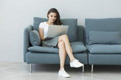 Mujer joven que usa la computadora portátil en el sofá Imagen de archivo libre de regalías