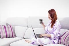 Mujer joven que usa la computadora portátil en el sofá en el país Imágenes de archivo libres de regalías