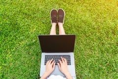 Mujer joven que usa la computadora portátil en parque Fotografía de archivo libre de regalías