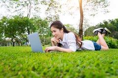 Mujer joven que usa la computadora portátil en parque Imágenes de archivo libres de regalías
