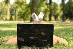 Mujer joven que usa la computadora portátil en parque Imagen de archivo