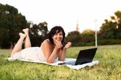 Mujer joven que usa la computadora portátil en parque Foto de archivo