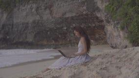 Mujer joven que usa la computadora portátil en la playa Funcionamiento del Freelancer de la muchacha metrajes