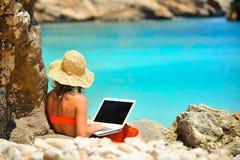 Mujer joven que usa la computadora portátil por el mar Foto de archivo