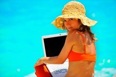 Mujer joven que usa la computadora portátil por el mar Foto de archivo libre de regalías