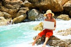Mujer joven que usa la computadora portátil por el mar Imágenes de archivo libres de regalías