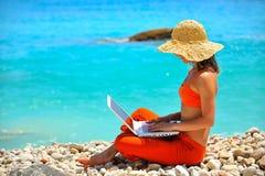 Mujer joven que usa la computadora portátil por el mar Imagenes de archivo