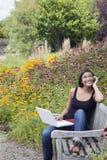 Mujer joven que usa la computadora portátil y el teléfono celular en parque imagen de archivo