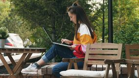 Mujer joven que usa la computadora port?til al aire libre metrajes