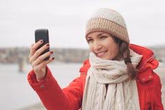 Mujer joven que usa la foto que toma móvil afuera Imagen de archivo libre de regalías