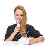 Mujer joven que usa la máscara del nebulizador para el asma respiratorio del inhalador Imagenes de archivo