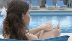 Mujer joven que usa la protección solar, teniendo resto, vacaciones en el hotel almacen de video