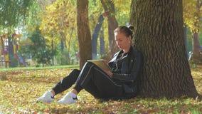 Mujer joven que usa la sentada al aire libre de la tableta en hierba Muchacha que usa la PC digital de la tableta en el parque de metrajes