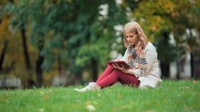 Mujer joven que usa la sentada al aire libre de la tableta en hierba y la sonrisa almacen de video