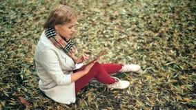 Mujer joven que usa la sentada al aire libre de la tableta en hierba y la sonrisa almacen de metraje de vídeo