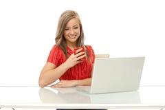Mujer joven que usa la sonrisa del ordenador portátil Fotografía de archivo