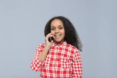 Mujer joven que usa la sonrisa feliz de la muchacha afroamericana de la llamada del teléfono elegante de la célula que habla que  Fotos de archivo