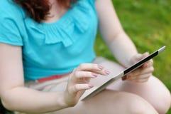 Mujer joven que usa la tableta fotografía de archivo libre de regalías