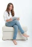 Mujer joven que usa la tableta digital Imagenes de archivo