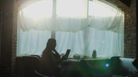 Mujer joven que usa la tableta en cafetería almacen de metraje de vídeo