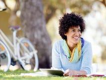 Mujer joven que usa la tableta en el parque Foto de archivo