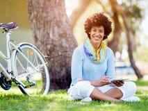 Mujer joven que usa la tableta en el parque Imagenes de archivo