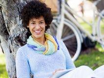 Mujer joven que usa la tableta en el parque Imagen de archivo libre de regalías