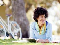 Mujer joven que usa la tableta en el parque Imágenes de archivo libres de regalías