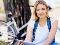 Mujer joven que usa la tableta en el parque Fotografía de archivo libre de regalías