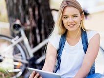 Mujer joven que usa la tableta en el parque Fotografía de archivo