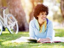 Mujer joven que usa la tableta en el parque Imagen de archivo
