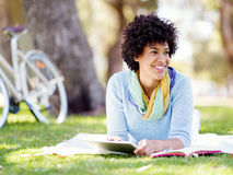 Mujer joven que usa la tableta en el parque Fotos de archivo