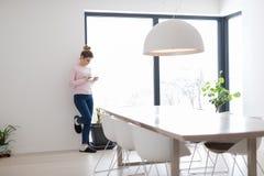 Mujer joven que usa la tableta en el piso Fotos de archivo