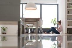 Mujer joven que usa la tableta en el piso Imagen de archivo libre de regalías