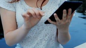 Mujer joven que usa la tableta en la cantidad del primer de la calle almacen de metraje de vídeo
