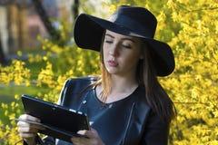 Mujer joven que usa la tableta en parque Fotografía de archivo libre de regalías