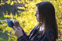 Mujer joven que usa la tableta en parque Imágenes de archivo libres de regalías