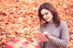 Mujer joven que usa la tableta en un parque fotografía de archivo libre de regalías