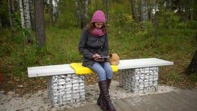 Mujer joven que usa la tableta mientras que se sienta en banco en parque del otoño Estudiante con una tableta que se sienta en el almacen de video