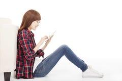 Mujer joven que usa la tableta y sentándose en el piso Foto de archivo