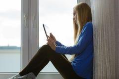 Mujer joven que usa la tablilla Fotografía de archivo libre de regalías