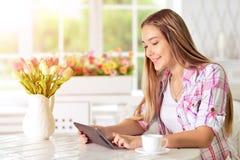 Mujer joven que usa la tablilla Imagen de archivo