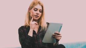 Mujer joven que usa la tablilla Fotos de archivo libres de regalías
