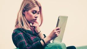 Mujer joven que usa la tablilla Imágenes de archivo libres de regalías
