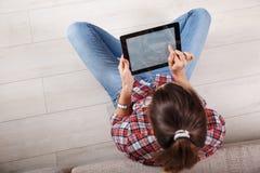 Mujer joven que usa la tablilla Foto de archivo libre de regalías