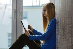 Mujer joven que usa la tablilla Imagenes de archivo
