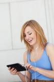 Mujer joven que usa la tablilla digital Fotografía de archivo
