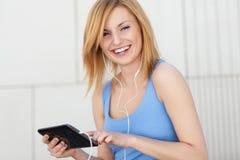 Mujer joven que usa la tablilla digital Fotos de archivo