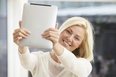 Mujer joven que usa la tablilla digital Imagen de archivo